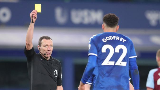 Wasit Kevin Friend (kiri) memberi kartu kuning kepada gelandang Everton, Ben Godfrey dalam laga lanjutan Liga Inggris 2020/21 pekan ke-17 melawan West Ham United di Goodison Park, Jumat (1/1/2021). Everton kalah 0-1 dari West Ham United. (AFP/Alex Pantling/Pool)