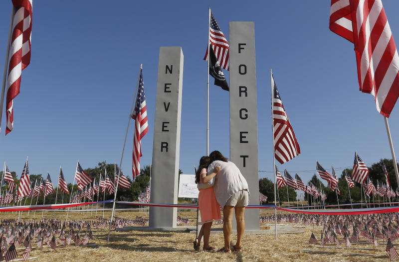 Rita Mariano and her daughter, Emily, 7, visit a memorial erected in honor of the 17th anniversary of the terrorist attacks on the United States, Tuesday, Sept. 11, 2018, in West Sacramento, Calif. (AP Photo/Rich Pedroncelli)