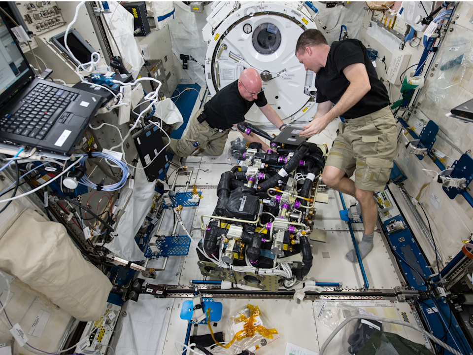 NASA astronauts Scott Kelly (left) and Terry Virts (right) work on a Carbon Dioxide Removal Assembly (CDRA) inside the station's Japanese Experiment Module (NASA)
