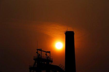 FILE PHOTO: The sun sets behind a chimney of a steel mill in Tangshan, Hebei province February 18, 2014. REUTERS/Petar Kujundzic/File Photo