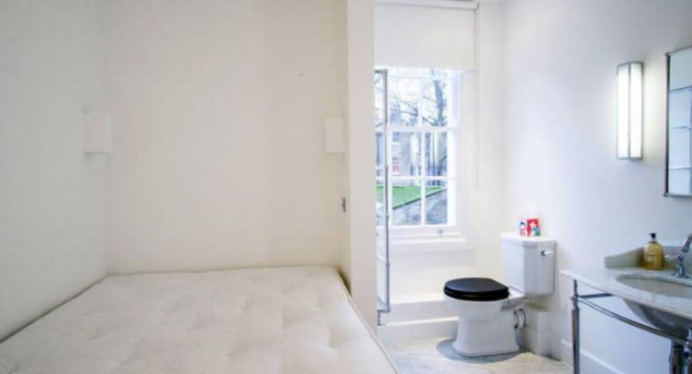 A bed pictured next to a toilet in a London apartment.