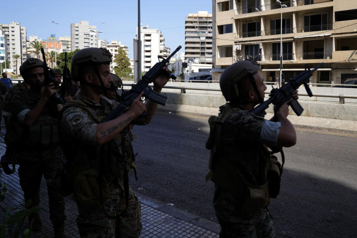 Lebanese army soldiers deploy during armed clashes that erupted during a protest in the southern Beirut suburb of Dahiyeh, Lebanon, Thursday, Oct. 14, 2021. It was not immediately clear what triggered the gunfire, but tensions were high along a former civil war front-line between Muslim Shiite and Christian areas. (AP Photo/Hassan Ammar)