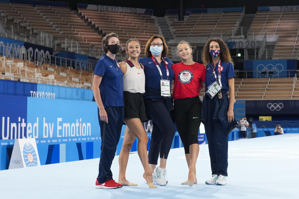 Laura Zeng, second from left, and Evita Griskenas, second from right, from the United States pose with their coaches after an individual rhythmic gymnastics training session at the 2020 Summer Olympics, Thursday, Aug. 5, 2021, in Tokyo, Japan. (AP Photo/Markus Schreiber)