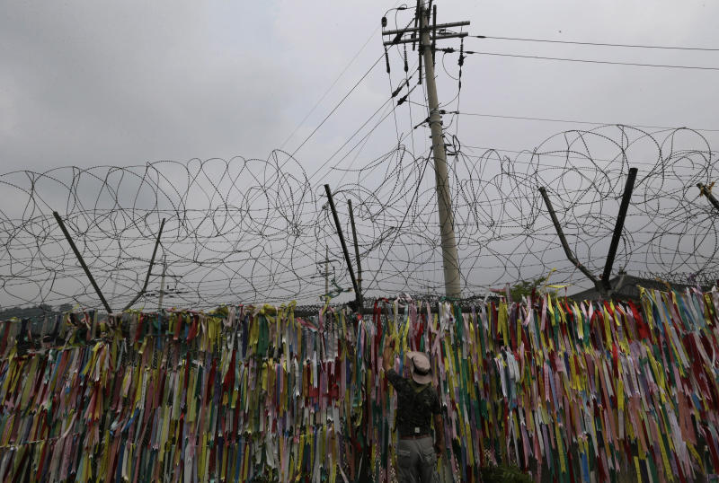 A man touches ribbons with messages wishing for North and South Koreas' reunification on military wire fences at the Imjingak Pavilion near the border village of Panmunjom, which has separated the two Koreas since the Korean War, in Paju, north of Seoul, South Korea, Wednesday, Aug. 7, 2013. (AP Photo/Lee Jin-man)