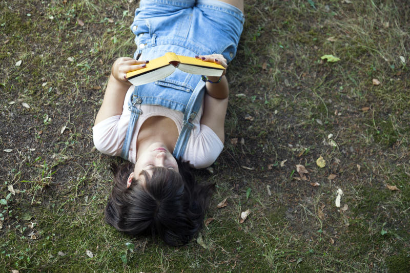 Teenager girl lying on the grass reading a book