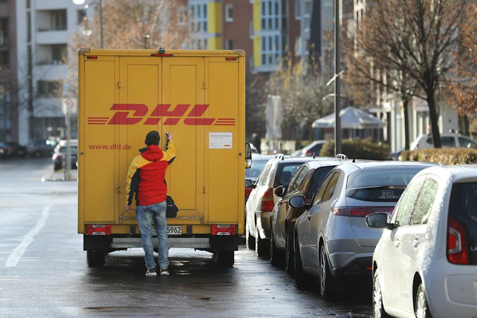 BERLIN, GERMANY - DECEMBER 04:  An employee of package delivery service DHL opens the door of a DHL truck on December 4, 2017 in Berlin, Germany. DHL, which belongs to German postal carrier Deutsche Post, is currently the target of a blackmailer. According to police the blackmailer sent two recent packages, one delivered to a pharmacy in Potsdam last Friday and one delivered in November in Frankfurt an der Oder. The one sent to Potsdam contained a very large firecracker and nails and, according to a recent police announcement, could have detonated. The blackmailer is reportedly demanding at least EUR 1 million and is threatening to send more explosive-laden packages.  (Photo by Sean Gallup/Getty Images)