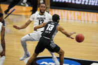 Colorado forward Dallas Walton (13) draws the charge from Georgetown guard Donald Carey (13) in the first half of a first-round game in the NCAA men's college basketball tournament at Hinkle Fieldhouse in Indianapolis, Saturday, March 20, 2021. (AP Photo/Michael Conroy)