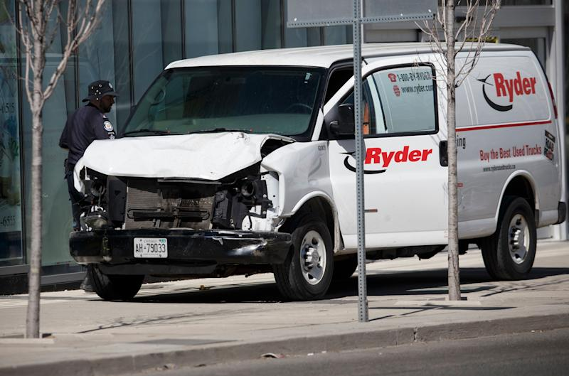 Police inspect a van suspected of being involved in a collision injuring at least eight people at Yonge Street and Finch Avenue in Toronto.