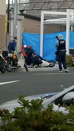 Police attend to the scene of a stabbing attack on a Japanese police officer near a police box in Suita, Japan in this still frame taken from social media video dated June 16, 2019