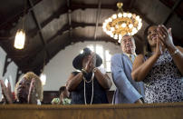 FILE - In this Sunday, July 10, 2016 file photo, parishioners clap during a worship service at the First Baptist Church, a predominantly African-American congregation, in Macon, Ga. There are two First Baptist Churches in Macon _ one black and one white. (AP Photo/Branden Camp)