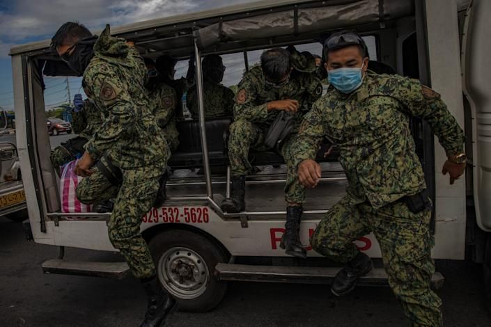 Filipino policemen wearing facemasks man a checkpoint as authorities begin implementing lockdown measures on March 16, 2020 in Las Pinas, Metro Manila, Philippines.