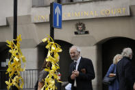 John Shipton, the father of WikiLeaks founder Julian Assange, looks at ribbons tied to a street sign by a supporter of his son outside the Central Criminal Court, the Old Bailey, in London, Monday, Sept. 14, 2020. The London court hearing on WikiLeaks founder Julian Assange's extradition from Britain to the United States resumed Monday after a COVID-19 test on one of the participating lawyers came back negative, WikiLeaks said Friday, (AP Photo/Matt Dunham)