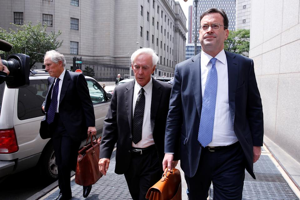 Billy Walters, center, seen here in 2016, has had his insider-trading conviction commuted by President Trump. (Reuters)