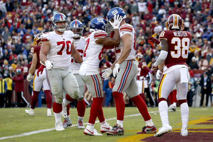 New York Giants wide receiver Sterling Shepard, center left, congratulates tight end Kaden Smith after he caught a touchdown pass from quarterback Daniel Jones during the second half of an NFL football game against the Washington Redskins, Sunday, Dec. 22, 2019, in Landover, Md. (AP Photo/Alex Brandon)