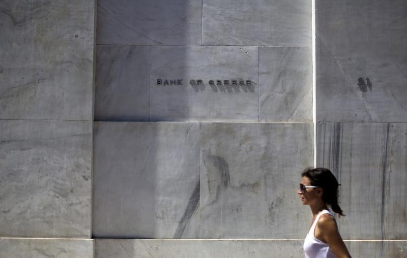 A woman walks past the headquarters of the Bank of Greece in Athens