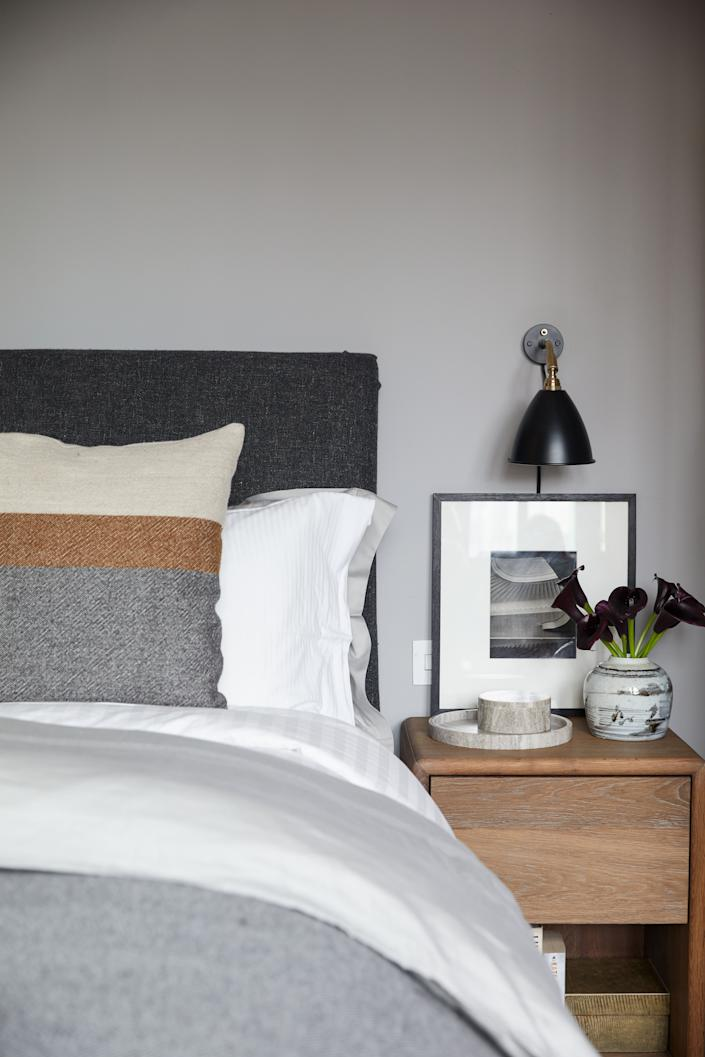 The bedding is from Belgian luxury linen company Libeco, and the sanded and smoked oak nightstand was designed by Basmajian. The wall lamp is from Original BTC, and the vase is Chinese 19th century. The photograph is by Karl Hugo Schmölz.
