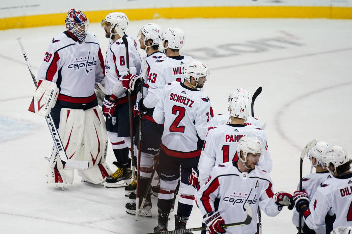 Washington Capitals' Ilya Samsonov (30) and Alex Ovechkin (8) celebrate with teammates after an NHL hockey game against the New Jersey Devils on Sunday, April 4, 2021, in Newark, N.J. The Capitals won 5-4. (AP Photo/Frank Franklin II)