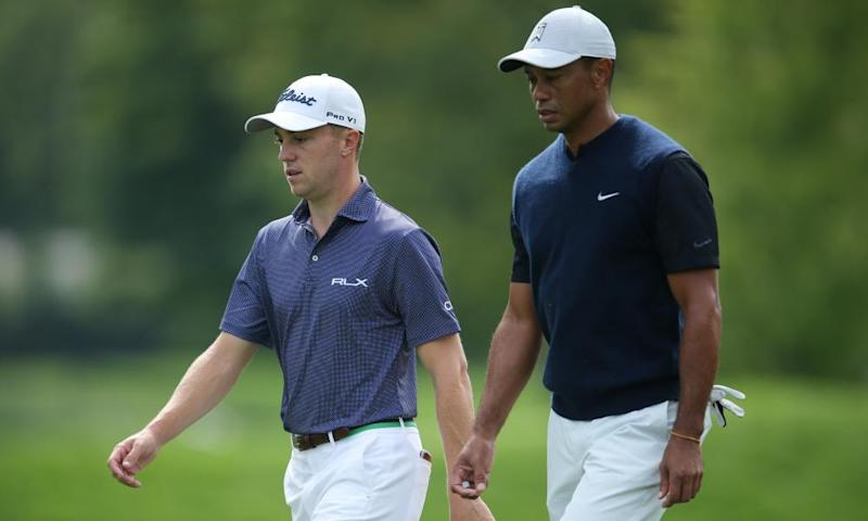Justin Thomas (left) and Tiger Woods walk down the 12th fairway during the first round.