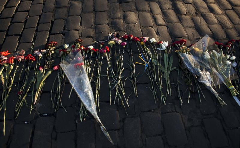 Flowers placed by people in memory of those who died in late February's clashes are lit by the early morning sun in Kiev's Independence Square, Ukraine, Tuesday, March 11, 2014. (AP Photo/David Azia)