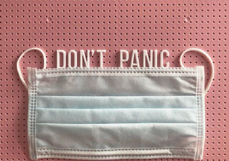 A pink noticeboard with a Don't Panic message, along with a facemask