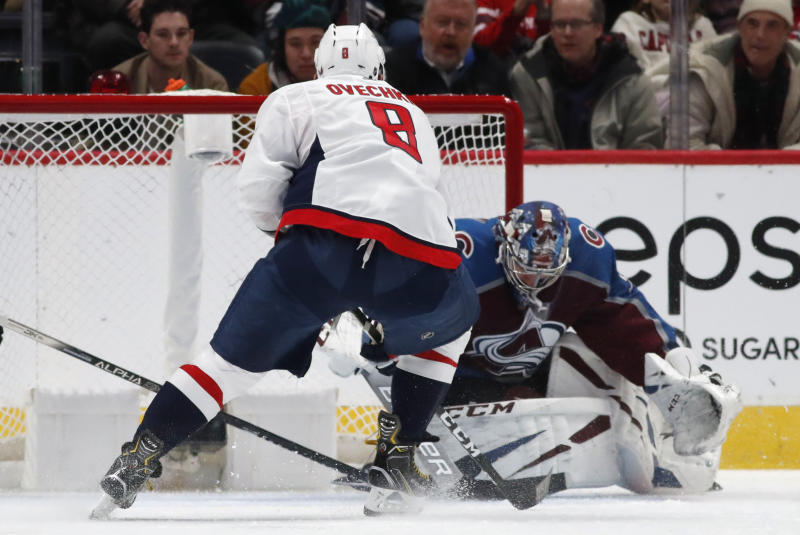 Washington Capitals left wing Alex Ovechkin, front, has his shot stopped by Colorado Avalanche goaltender Philipp Grubauer during the third period of an NHL hockey game Thursday, Feb. 13, 2020, in Denver. The Capitals won 3-2. (AP Photo/David Zalubowski)