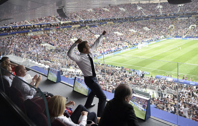 French President Emmanuel Macron is on his feet after France won the World Cup