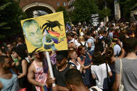 People taking part in a gay pride parade hold a banner depicting Hungarian Prime Minister Viktor Orban in Budapest, Hungary, Saturday, July 24, 2021. Hungary's government led by right-wing Prime Minister Viktor Orban passed a law in June prohibiting the display of content depicting homosexuality or gender reassignment to minors, a move that has ignited intense opposition in Hungary while EU lawmakers have urged the European Commission to take swift action against Hungary unless it changes tack. (AP Photo/Anna Szilagyi)