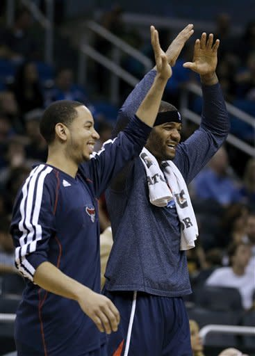 Atlanta Hawks' Devin Harris, left, and Josh Smith come off the bench during a time out to celebrate during the final minutes of an NBA basketball game against the Orlando Magic, Wednesday, Feb. 13, 2013, in Orlando, Fla. Atlanta won 108-76.(AP Photo/John Raoux)