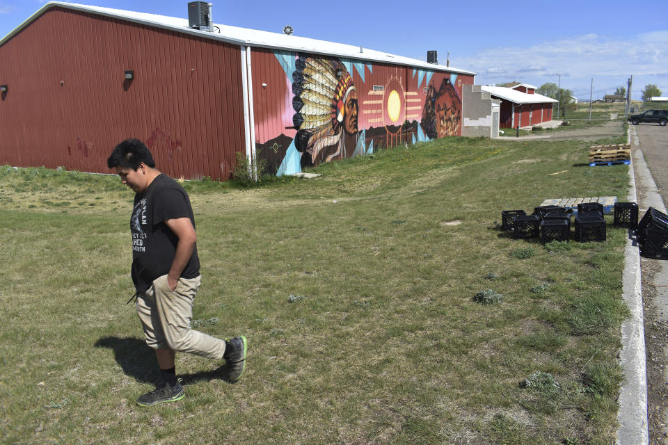 In this Thursday, May 20, 2021, photo, a young man walks past the U.S. Post Office on the Standing Rock Sioux Reservation in Cannon Ball, N.D. Oil pumped from Native American lands in the U.S. increased about tenfold since 2009 to more than 130 million barrels annually, bringing new wealth to about a dozen tribes. Tribes left out of the drilling boom have become outspoken against fossil fuels as climate change impacts worsen. (AP Photo/Matthew Brown)