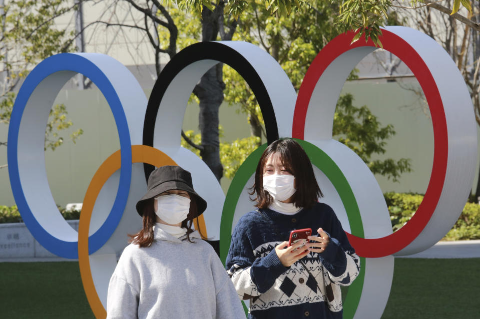 People walk past the Olympic rings in Tokyo, Wednesday, March 17, 2021. Organizers plan to exercise extreme caution when the Olympic torch relay starts next week. They know any stumble could imperil the opening of the Tokyo Games in just four months.  (AP Photo/Koji Sasahara)