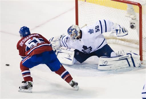 Toronto Maple Leafs goaltender Jonas Gustavsson, right, makes a save against Montreal Canadiens' David Desharnais during second period NHL hockey game action in Montreal, on Saturday, March 3, 2012. (AP Photo/The Canadian Press, Graham Hughes)