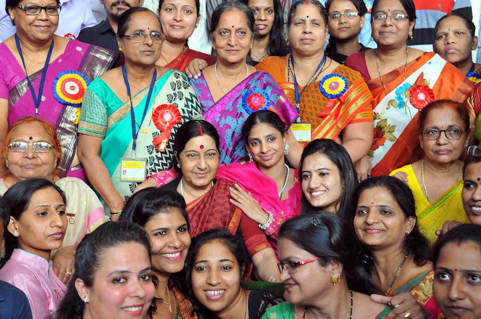 Sushma Swaraj and Geeta pose for pictures with their friends and faculty at Indore Deaf Bilingual Academy (IDBA) on November 23, 2015. (Photo by Shankar Mourya/Hindustan Times via Getty Images)