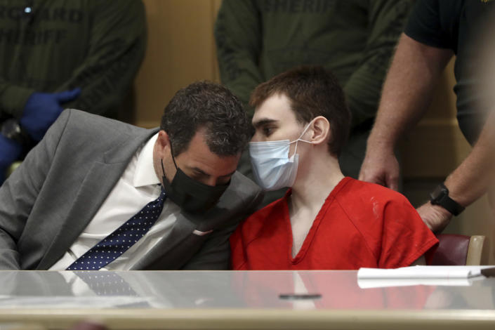 Parkland school shooter Nikolas Cruz, right, speaks to defense attorney Gabe Ermine during a pre-trial hearing at the Broward County Courthouse in Fort Lauderdale, Fla., Wednesday, July 14, 2021, on four criminal counts stemming from his alleged attack on a Broward jail guard in November 2018. Cruz is accused of punching Sgt. Ray Beltran, wrestling him to the ground and taking his stun gun. (Amy Beth Bennett/South Florida Sun-Sentinel via AP, Pool)