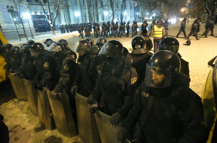 Ukrainian riot police guard Ukrainian government buildings in Kiev, Ukraine, early Tuesday, Dec. 10, 2013. Heavily armed riot troops broke into the offices of a top Ukrainian opposition party in Kiev and seized its servers Monday, the party said, as anti-government protests crippled the capital for yet another day. Elsewhere police dismantled or blocked off several small protest tent camps set up near key national government buildings in the city. (AP Photo/Sergei Grits)