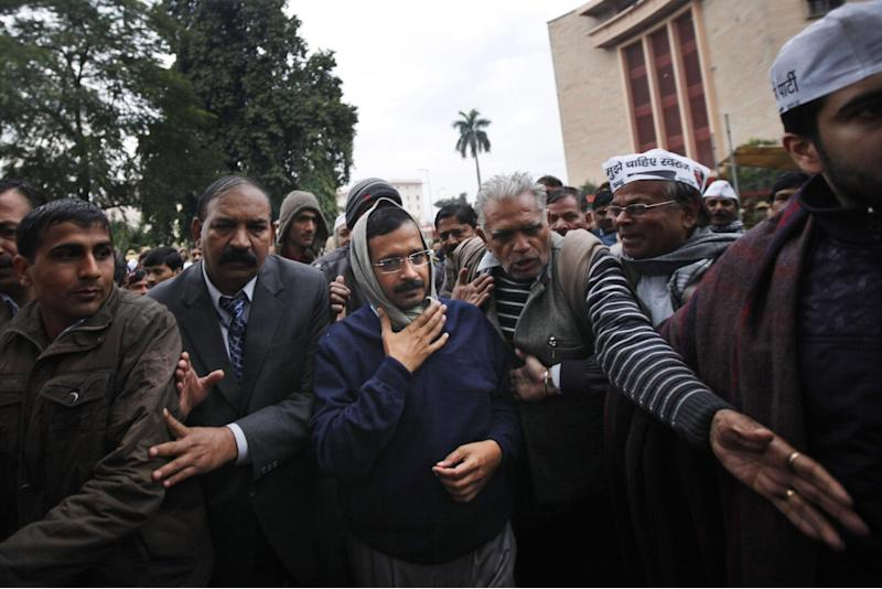 New Delhi Chief Minister Arvind Kejriwal, center, is escorted by supporters and security men during a demonstration against the police in New Delhi, India, Tuesday, Jan. 21, 2014. For a decade, Kejriwal has tilted at India's many windmills. He has led protests and hunger strikes against government corruption.But now he is the top official of the Indian capital, an activist suddenly elevated to power. And just a little over a month after his surprise win in city elections, he has launched yet another protest. Even if it's not always clear what he is demanding. (AP Photo/Altaf Qadri)