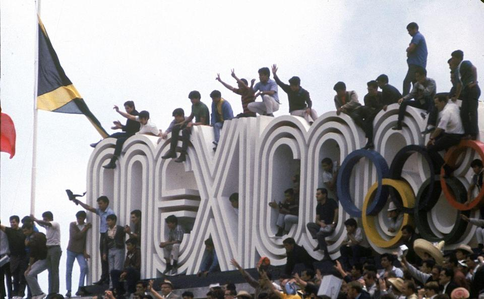<p>Crowds climb on top of Mexico's Olympic sign during the opening ceremony of the 1968 Summer Olympics in Mexico City. This marks the first time the Olympics were broadcasted in color. </p>