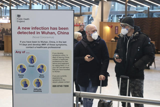 People arrive at Heathrow airport wearing protective face masks following the coronavirus outbreak (AP)