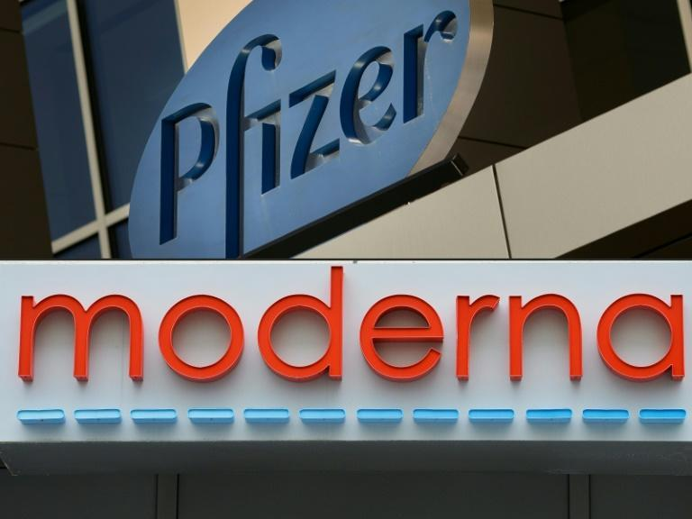 This combination of file pictures shows signs for the Pfizer and Moderna pharmaceutical companies, both in Cambridge, Massachusetts; executives at both, as well as at Novavax, have raised questions by selling shares worth millions amid the pandemic