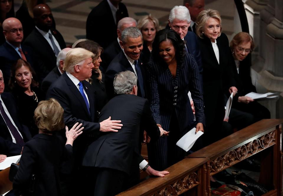President George W. Bush reaches across in front of President Donald Trump and first lady Melania Trump to greet former President Barack Obama and former first lady Michelle Obama, sitting in the front row with former President Bill Clinton, former first lady Hillary Clinton and former first lady Rosalynn Carter as he arrives at the state funeral for his father former President George H.W. Bush at the Washington National Cathedral in Washington, D.C., Dec. 5, 2018. (Photo: Kevin Lamarque/Reuters)