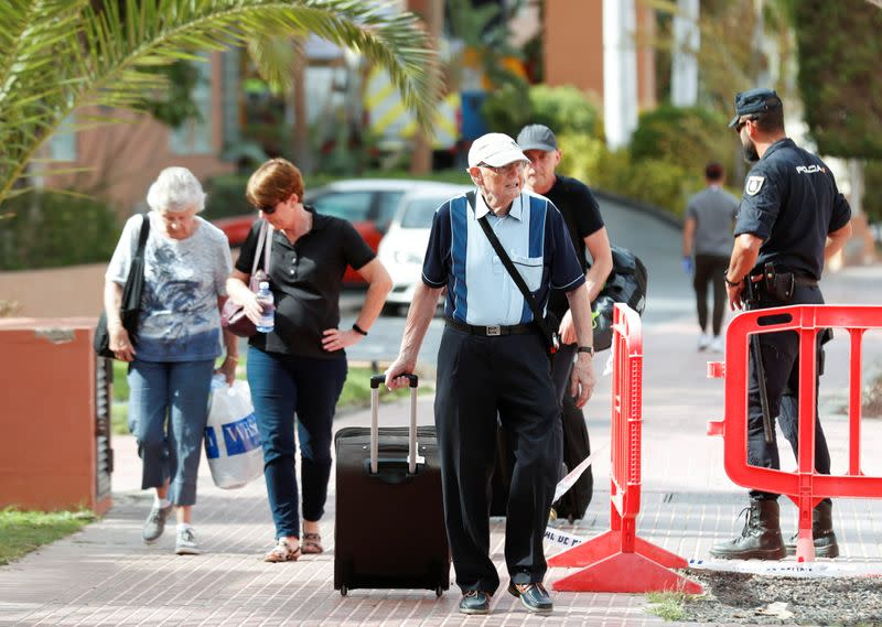 Tourists leave the hotel H10 Costa Adeje Palace, which is on lockdown after novel coronavirus has been confirmed in Adeje