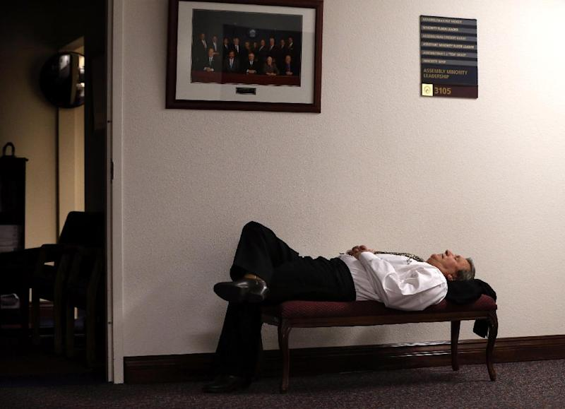 Nevada Assemblyman John Ellison, R-Elko, naps after lawmakers failed to meet their midnight deadline for the end of the 77th Legislative session in Carson City, Nev., Tuesday, June 4, 2013. Gov. Brian Sandoval called the Legislature back into a special session to address a handful of issues, which some lawmakers said they missed finishing by minutes. (AP Photo/Cathleen Allison)