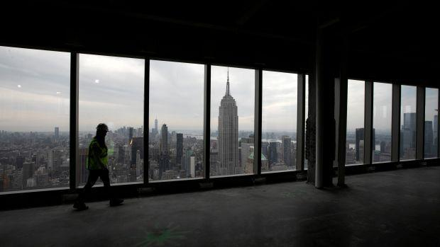 A person walks through an empty floor of an office tower in New York City that faces the Empire State Building, framed in the center of a window.
