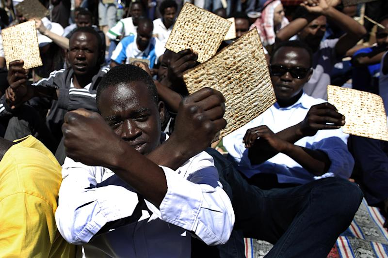 African migrants hold matzo, unleavened bread traditionally eaten by Jews during the week-long Passover holiday, as they protest outside the Holot detention center, southern Israel, Friday, April 11, 2014. Hundreds of African migrants gathered in Israel's Negev desert on Friday to eat matzo and recall the Passover story - one of freedom from bondage - mere steps away from a detention facility where they are being held. (AP Photo/Tsafrir Abayov)