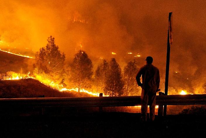 A firefighter watches as flames approach Highway 20 during the Rocky fire near Clear Lake, California on August 2, 2015 (AFP Photo/Josh Edelson)