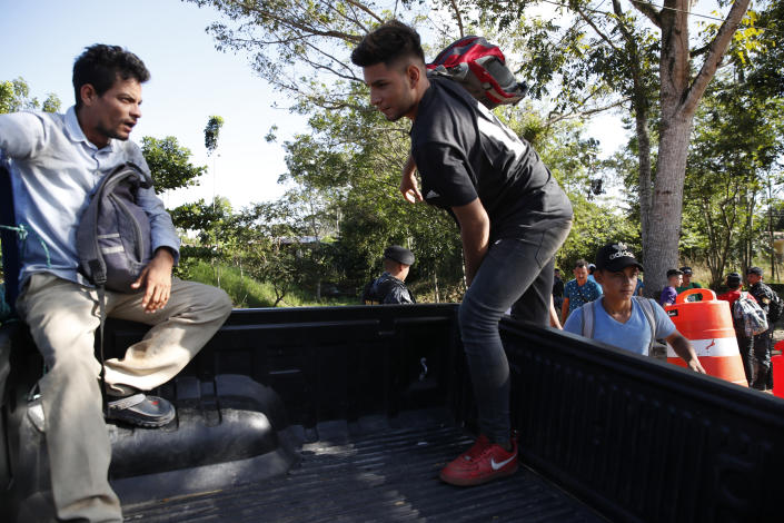 Honduras migrants trying to reach the United States get in the bed of a police pickup truck before return to Honduran border, in Morales, Guatemala, Wednesday, Jan. 15, 2020. Hundreds of mainly Honduran migrants started walking and hitching rides Wednesday from the city of San Pedro Sula and crossed the Guatemala border in a bid to form the kind of migrant caravan that reached the U.S. border in 2018. (AP Photo/Moises Castillo)