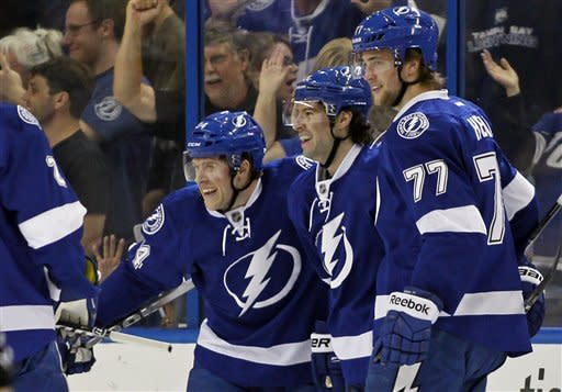 Tampa Bay Lightning's Victor Hedman, right, of Sweden, celebrates his goal with teammates J.T. Wyman, left, and Nate Thompson during the first period of an NHL hockey game against the Boston Bruins on Tuesday, March 13, 2012, in Tampa, Fla. (AP Photo/Mike Carlson)