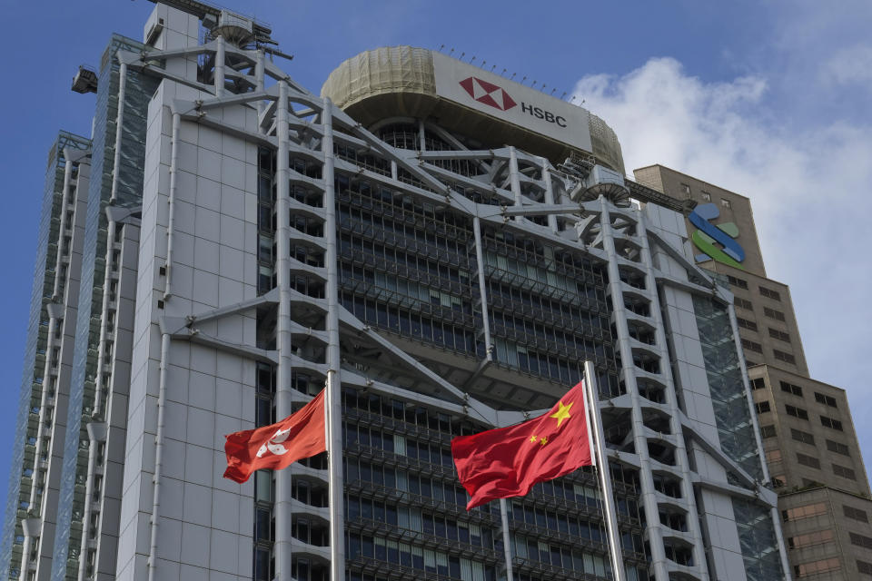 In this Wednesday, Sept. 8, 2021, photo, China mainland and Hong Kong flags are raised in front of the HSBC headquarters in Hong Kong. Banks in Hong Kong, Macao and China's Guangdong province can expect to launch investment products that are open to residents in these areas as soon as October, according to Hong Kong's monetary authority. (AP Photo/Kin Cheung)