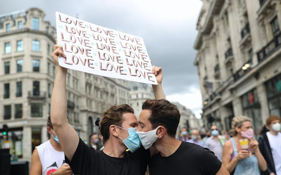 Demonstrators wearing face masks kiss as they take part in the Gay Liberation Front (GLF) pride march in London, Britain, June 27, 2020.