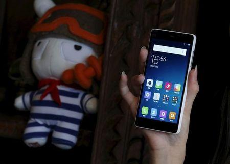 A model displays a newly launched Xiaomi Mi 4i phone in Hong Kong