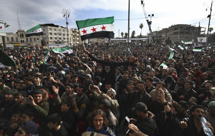 Thousands of anti-Syrian government protesters shout slogans and wave revolutionary flags, to mark 10 years since the start of a popular uprising against President Bashar Assad's rule, that later turned into an insurgency and civil war, In Idlib, the last major opposition-held area of the country, in northwest Syria, Monday, March 15, 2021. (AP Photo/Ghaith Alsayed)